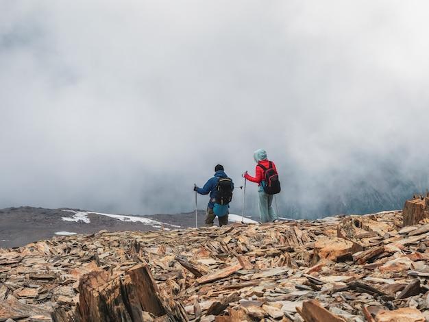 선택적 초점입니다. 남자와 여자는 안개 낀 눈 언덕 꼭대기에 올라갑니다. 팀워크와 승리, 어려운 상황에 처한 사람들의 팀워크. 산 정상까지 힘든 등반.