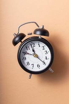 선택적 초점. 손과 숫자가있는 똑딱 거리는 검은 색 시계. 부드러운 커피 단색 배경에