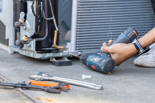 Селективный фокус ремонт кондиционеров, техник руками человека с помощью отвертки, крепящей современную систему кондиционирования