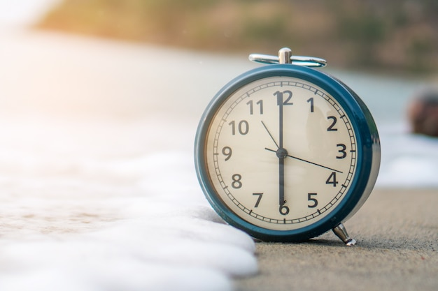 Selective focus of alarm clock with nature background.
