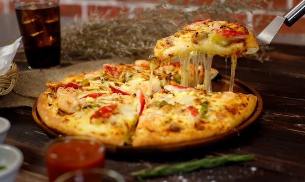 Селективный фокус и крупным планом на кусок домашней пиццы из морепродуктов с двойным сыром на шпатель или совок с размытым фоном деревянного стола, холодного напитка и кирпичной стены. концепция питания.