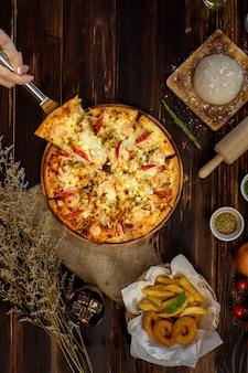 Селективный фокус и крупным планом кусок пиццы на лопатке или совке вручную, держа или представляя с размытием деревянного фона и украшенный мешковиной, ингредиентами, жареным картофелем и холодным напитком.