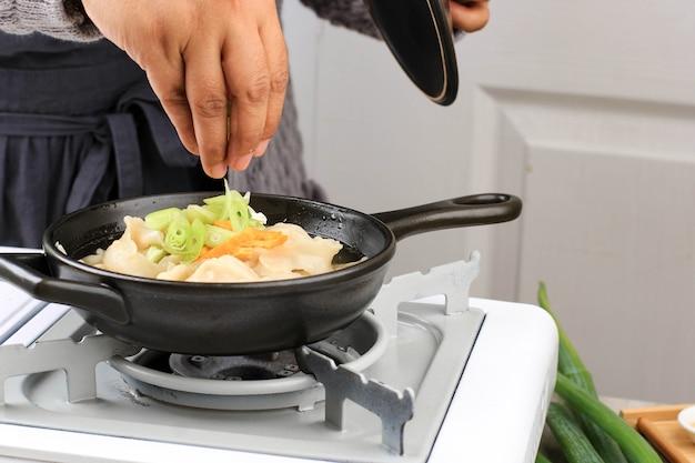セレクティブフォーカスアジア女性ホームシェフクッキング点心スープマンドゥグク、ネギのトッピングとストーブの上にスライスした目玉焼きを添えた韓国の餃子スープ。スライスしたネギを入れる