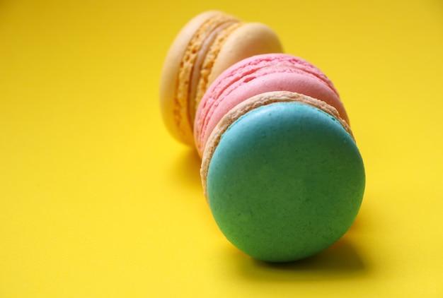 黄色の背景にマカロンパステルカラースナックと甘い食べ物のグループでの選択的な焦点