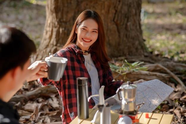 Селективный фокус на улыбающейся женщине, молодая пара звонит кофейными кружками со счастливым вместе утром перед палаткой для кемпинга утром в природном парке