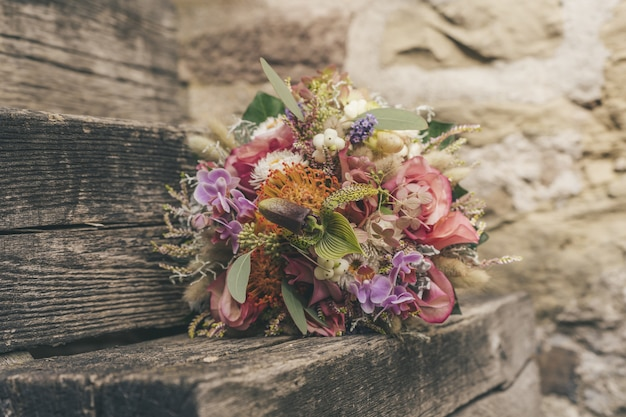 Selective focus  of a beautiful small flower bouquet on a wooden surface