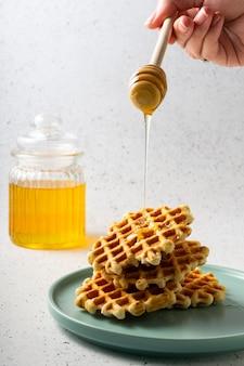 선택적 초점, 파란색 접시에 꽃 꿀 벨기에 설탕 와플 프리미엄 사진