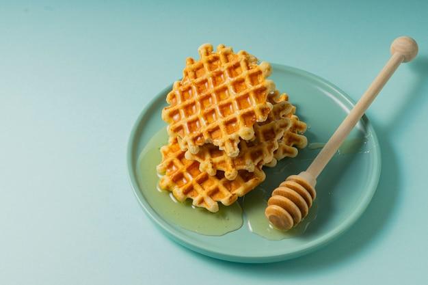 선택적 초점, 파란색 접시에 꽃 꿀 벨기에 설탕 와플