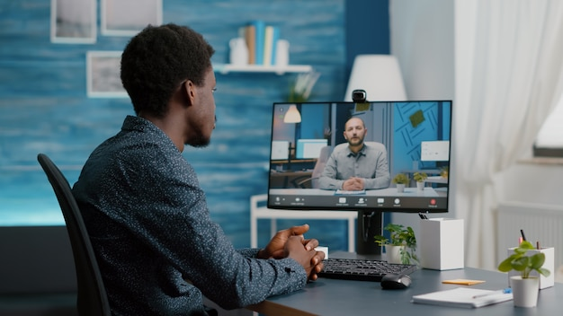 Selective focus on black guy using online conference video call talking with his work colleague