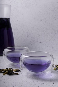 Selective focus, blue flower tea with dry flowers, in clear cups with double glass