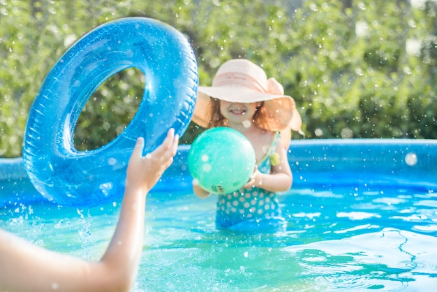 Selective focus, blur devokus. children play with a ball in the pool in hot summer. girl and boy outdoors