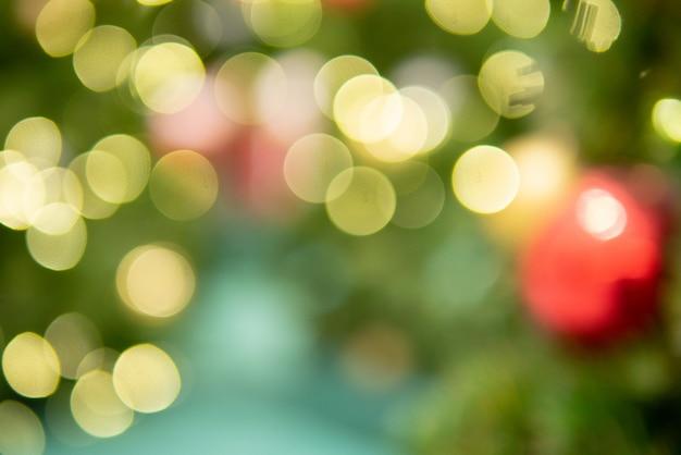 セレクティブフォーカス照明付きのお祭りを祝うためのクリスマスツリーの背景のボケ味