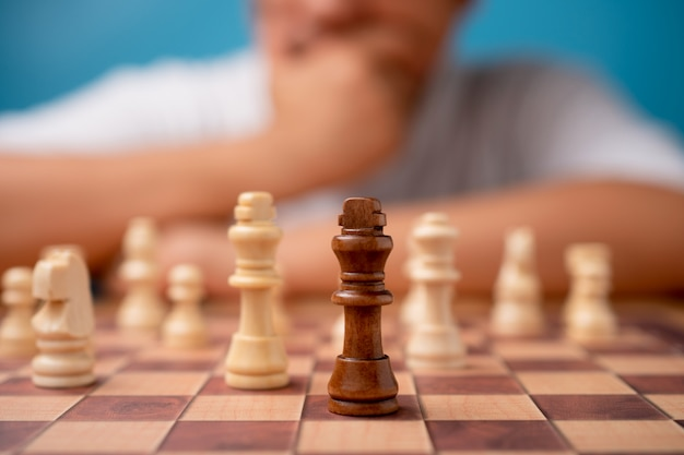 Selective focus of brown king chess and businessman thinking strategy and competitor evaluation in competition.