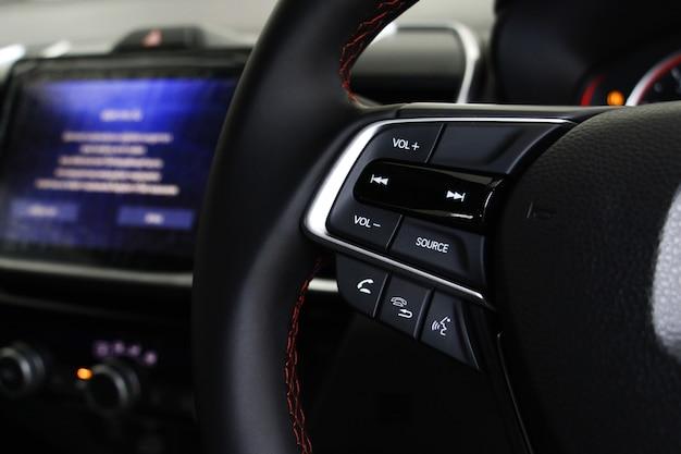 車のコンソールにぼやけた画面表示のある車のステアリングホイールの選択フォーカスボタン。車のコンセプトのシステム。