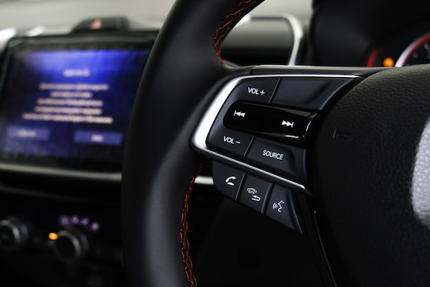 Selective focus button on steering wheel in car with blurry screen display on console of car. system in car concept.