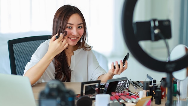 Selective focus on camera, young and beautiful asian girl shows how to use face brush to camera with smile and happy during broadcast video recording about cosmetics content and review.