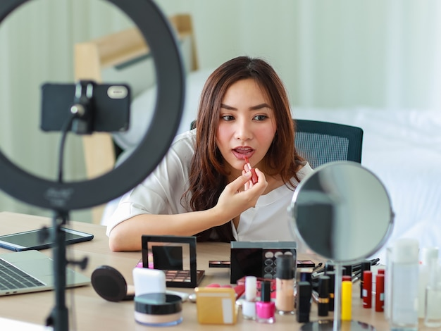 Selective focus on camera, young and beautiful asian girl shows make-up how to use lipstick to camera with smile and happy during broadcast video recording about cosmetics content and review.