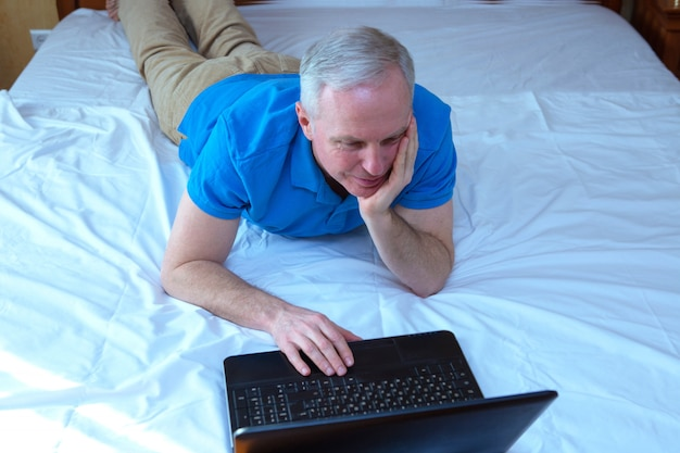 Selective focus on caucasian man lying in bed and watching something on laptop