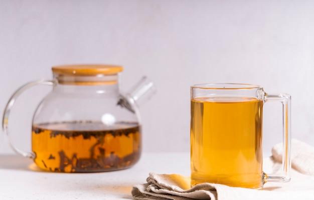 Выборочный фокус: цейлонский черный чай в прозрачной кружке на светлом столе copyspace. горизонтальное положение. минималистичный стиль