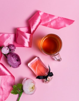 Selective focus: ceylon black tea in a transparent mug on a pink table with a pink satin ribbon. women's perfume and flowers.