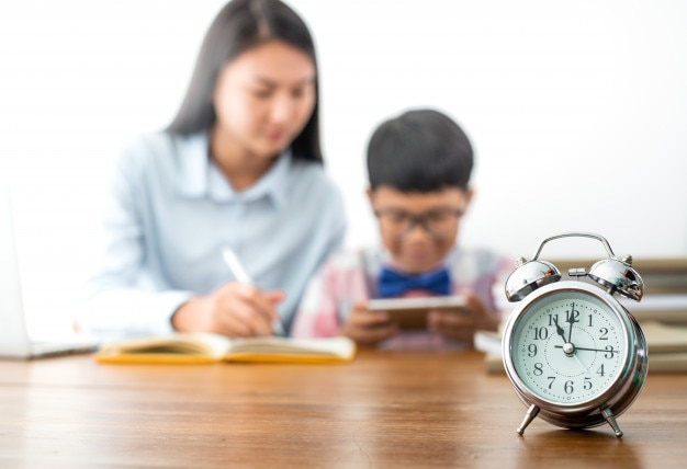 Selective focus at clock, boy using mobile phone playing game while homework not finished