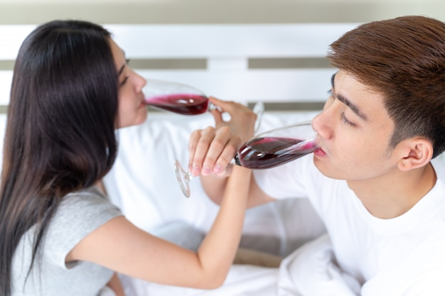 Selective focus and close up hand of young couple holding glass of wine in the bedroom