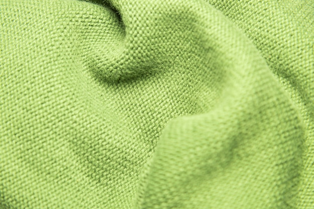 Selective focus and close up view of green knitting wool texture.