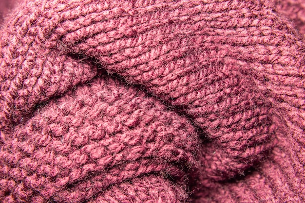 Selective focus and close up view of red knitting wool texture.