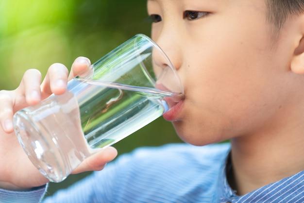選択的な焦点、庭のガラスから水を飲む若いアジアの少年をクローズアップ