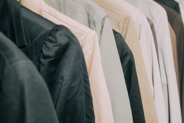 Selective focus coats and suits hanged on a clothes rack.