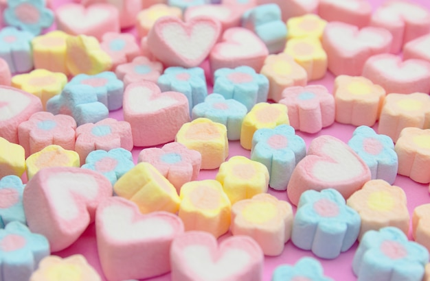 Selective focus colorful fluffy marshmallows on pink background, sweet dessert fudge