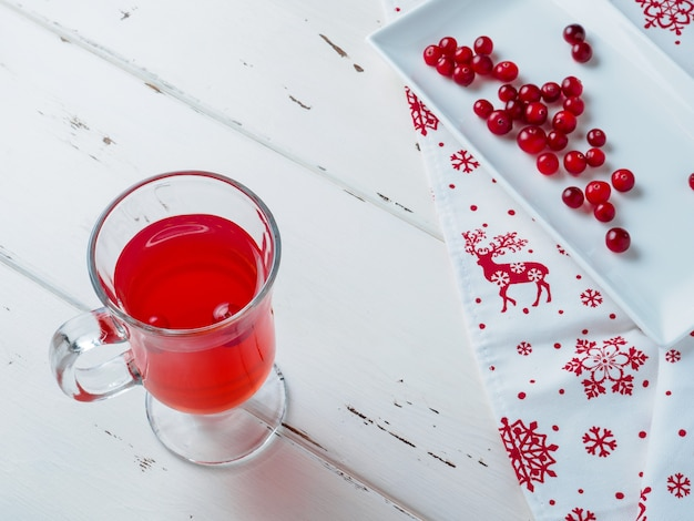Selective focus on cranberries in a fresh drink in a glass cup. berries on a white rectangular ceramic plate and a napkin with a new year's ornament.
