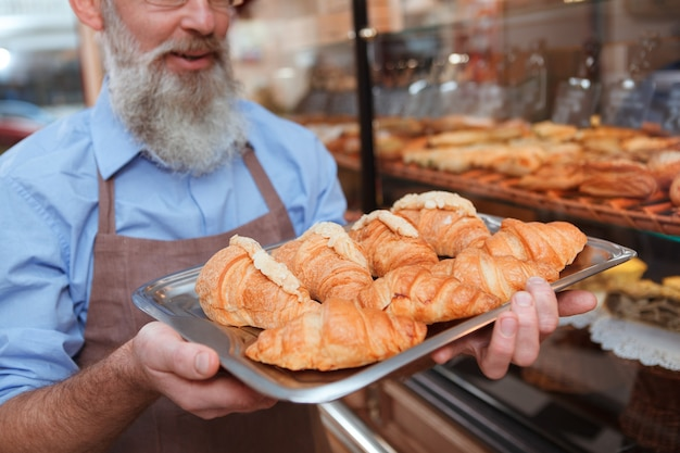 Selective focus on croissants on the tray in the hands of senior bearded baker