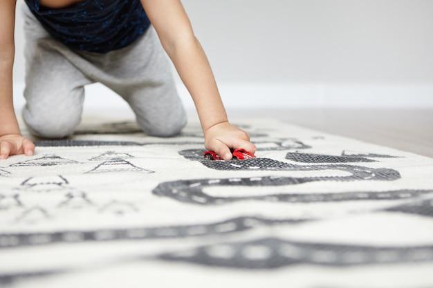 선택적 초점. 카펫에 그의 무릎에 서있는 빨간색 장난감 자동차를 가지고 노는 어린 백인 소년의 자른 된 초상화.