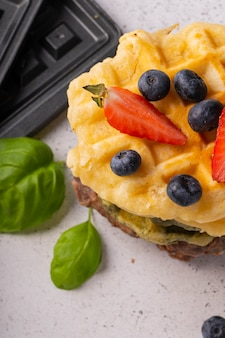Selective focus, curd waffles with vanilla and fresh berries on a light background