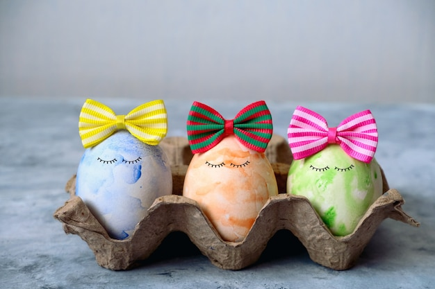 Selective focus cute blue, orange and green easter eggs in funny bows