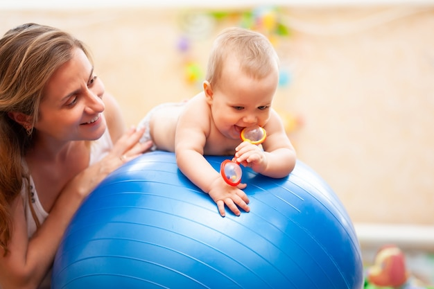 Selective focus of cute little toddler lying on big blue fitness ball and holding red toy