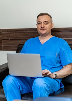 Selective focus on doctor in blue scrubs. sitting on sofa with laptop.