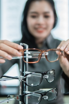 Selective focus of eyeglass frames placed on a shelf by a woman customer after trying them out at an optician