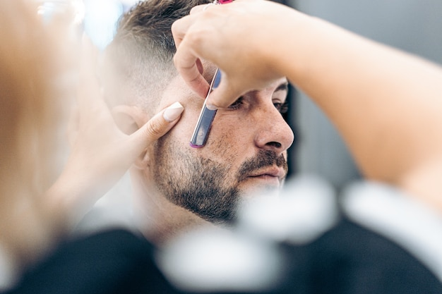 Selective focus on the face of a costumer being shaved by hand with a razor in a salon