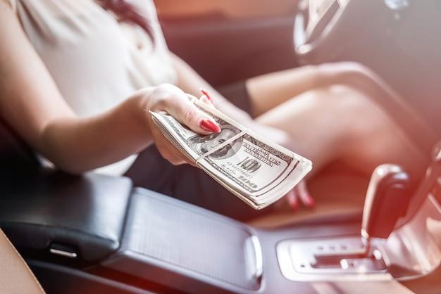 Selective focus on female hand with dollar bundle inside car