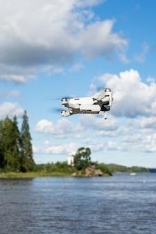 Селективный фокус, летающий дрон, квадрокоптер, на фоне летней природы и зелени