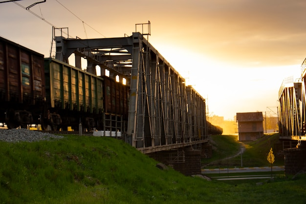 セレクティブフォーカス。電車に引っ張られた鉄道橋の貨車。夕方の日光と金属構造からのオレンジ色の夕方の光の反射。