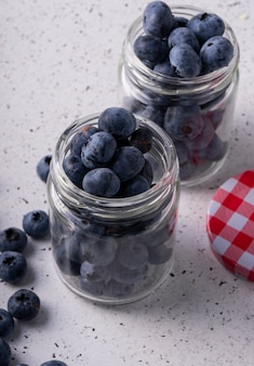 Selective focus, fresh blueberries in a twist glass jar with a lid. on light background