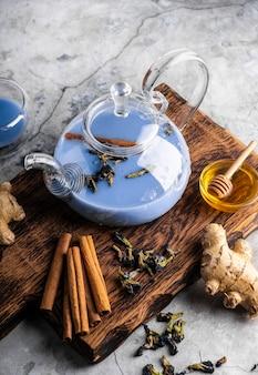 Селективный фокус свежезаваренный голубой чай масала в прозрачном чайнике с фруктами и свежими ягодами ...