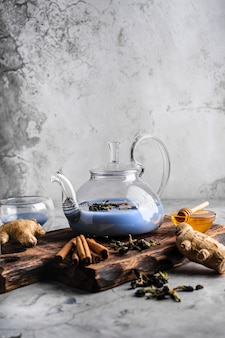 Selective focus freshly brewed blue masala tea in a transparent teapot with fruits and fresh berries...