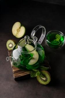 Селективный фокус, свежезаваренный зеленый чай с киви и мятой в прозрачном чайнике, с фруктами и свежими ягодами. листовой чай и специи. натюрморт. для рекламы и меню