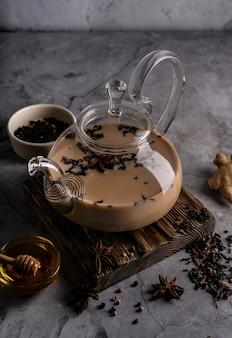 Селективный фокус, свежезаваренный чай масала в прозрачном чайнике, с фруктами и свежими ягодами. листовой чай и специи. натюрморт. для рекламы и меню