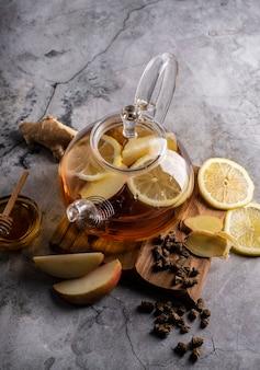 Селективный фокус свежесваренного чая в прозрачном чайнике с фруктами и свежими ягодами листового чая и ...