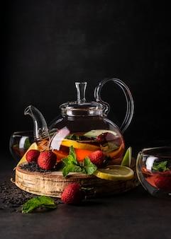 Селективный фокус свежезаваренного чая в прозрачном чайнике с фруктами и свежими ягодами листового чая и ...